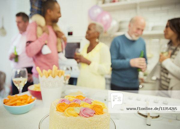 Family enjoying party behind cake