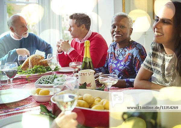 Portrait lächelnde Seniorin beim Weihnachtsessen mit der Familie am Tisch
