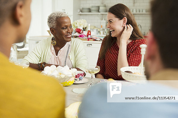 Lächelnde Frauen genießen die Party bei Tisch