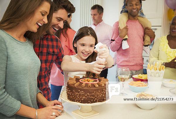 Lächelndes Familienglasurschokoladenkuchen in der Küche