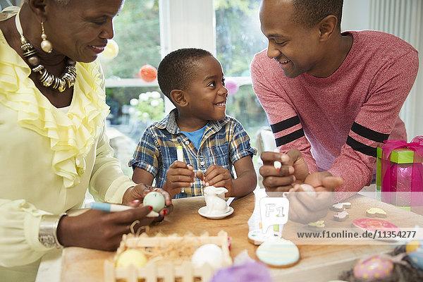 Mehrgenerationen-Familie beim Dekorieren von Ostereiern und Keksen