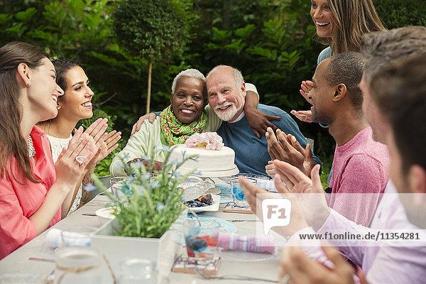 Zärtliches  multiethnisches Seniorenpaar umarmt sich und feiert Jubiläum am Verandatisch.