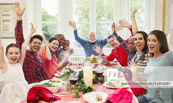 Portrait begeisterte multiethnische Mehrgenerationen-Familie winkt am Weihnachtstisch