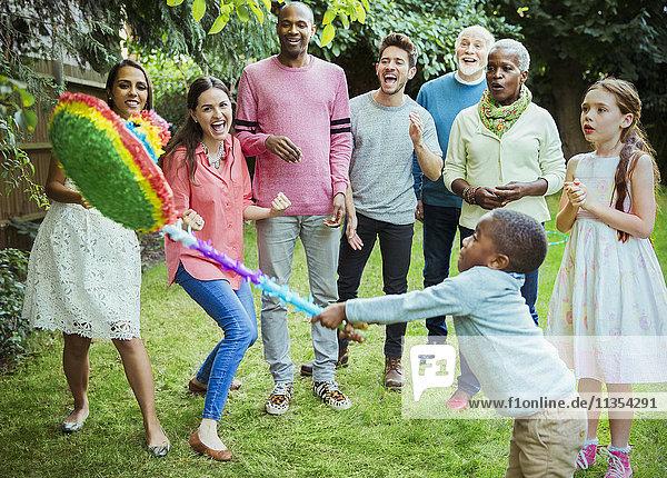 Multi-ethnische Mehrgenerationen-Familienjubeljubel bei der Geburtstagsparty auf Pinata