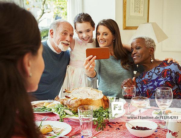 Multi-ethnische Mehrgenerationen-Familie mit Fotohandy  die Selfie am Weihnachtstisch mitnimmt.