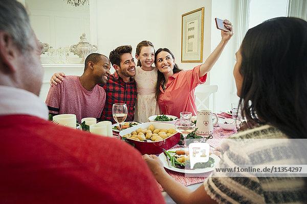 Multi-ethnische Familie mit Fotohandy  die Selfie am Weihnachtstisch nimmt.