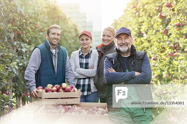 Portrait lächelnde Bauern bei der Apfelernte im Obstgarten Portrait lächelnde Bauern bei der Apfelernte im Obstgarten