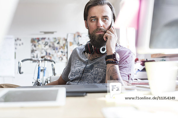 Pensive design professional with headphones talking on cell phone at desk