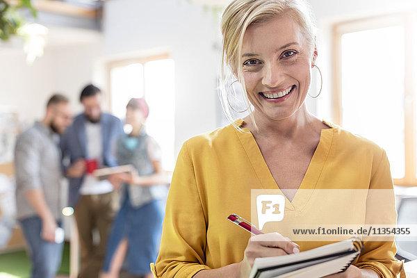 Portrait lächelnde Designerin mit Notizen im Notizbuch im Büro