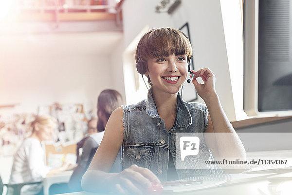 Lächelnder Designprofi mit Headset und Mikrofon im Büro