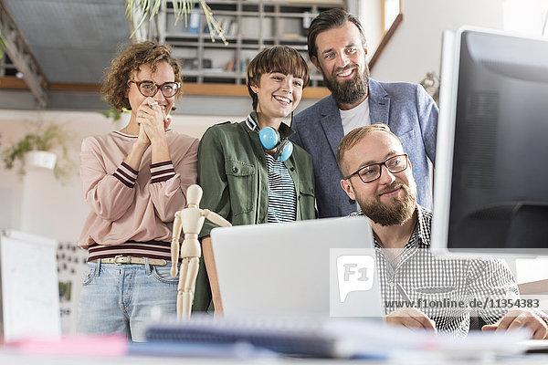 Lächelnde Designprofis treffen sich am Computer im Büro