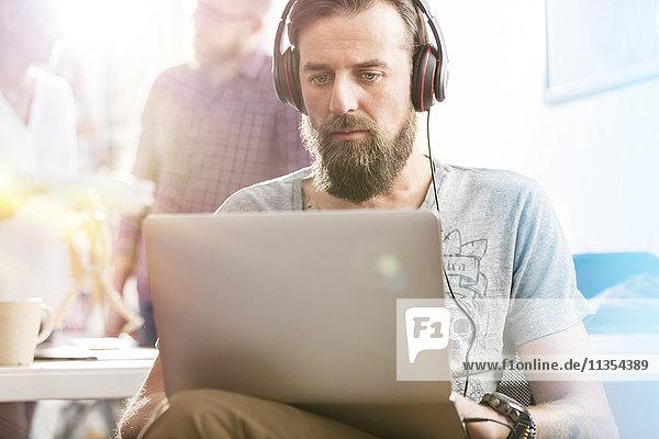 Serious männlichen Design-Profi mit Kopfhörer mit Laptop im Büro