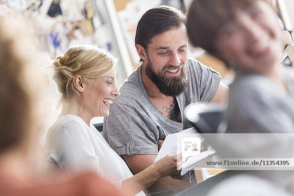 Lächelnde Designprofis treffen sich und besprechen den Papierkram im Büro.