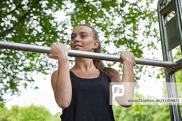 Junge Frau  die im Park trainiert und Klimmzüge an Übungsstangen macht Junge Frau, die im Park trainiert und Klimmzüge an Übungsstangen macht