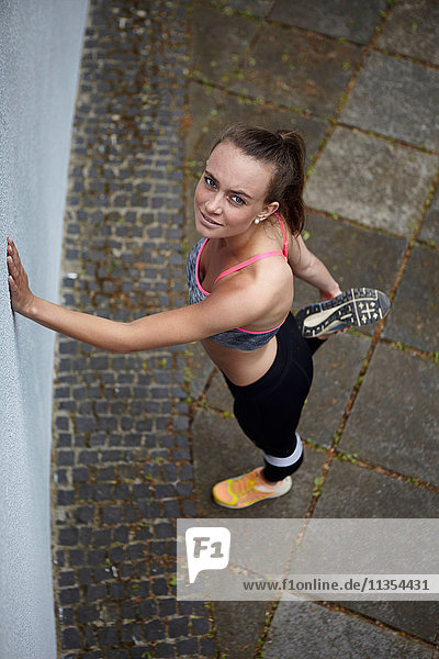Portrait einer jungen Frau beim Training  die Aufwärmübungen macht Portrait einer jungen Frau beim Training, die Aufwärmübungen macht