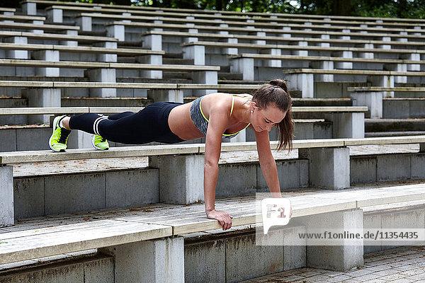 Junge Frau trainiert  macht Push-Ups auf der Stadiontreppe Junge Frau trainiert, macht Push-Ups auf der Stadiontreppe