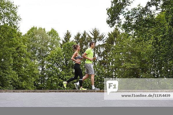 Junger Mann und Frau trainieren  laufen auf der Mauer Junger Mann und Frau trainieren, laufen auf der Mauer