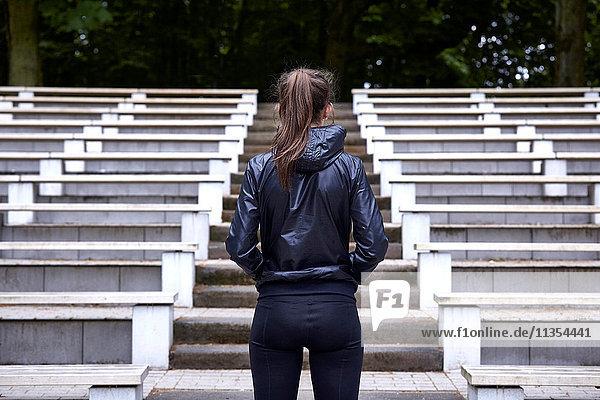 Rückansicht einer jungen Frau beim Training  die sich darauf vorbereitet  die Stadiontreppe hinaufzulaufen Rückansicht einer jungen Frau beim Training, die sich darauf vorbereitet, die Stadiontreppe hinaufzulaufen