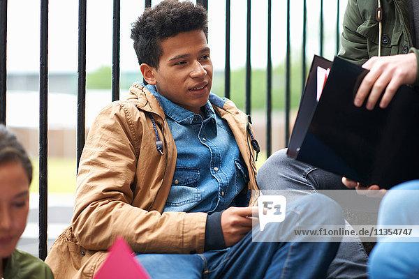 Junge erwachsene College-Studenten beim Chatten und Lernen auf dem Campus