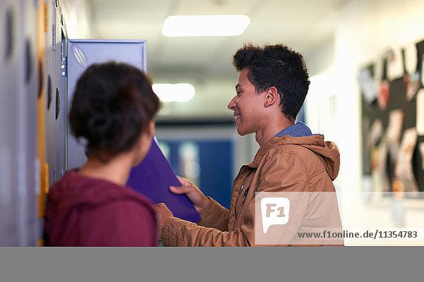 Junger männlicher Student entfernt Akte aus dem Schließfach des Colleges