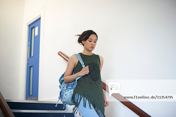 Young female college student moving down stairway