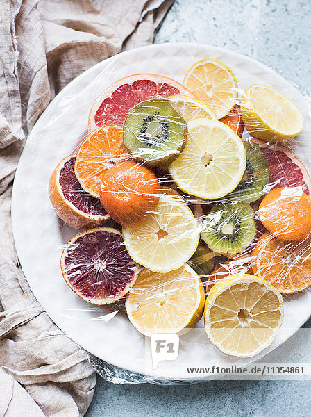 Overhead view of sliced citrus fruits served and covered on plate