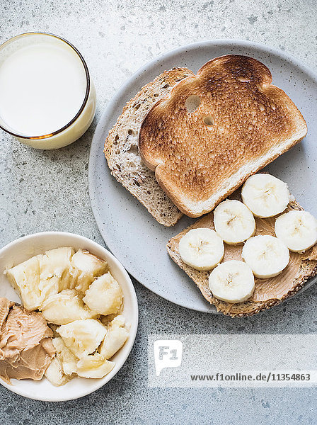 Draufsicht auf Toast mit Erdnussbutter  Banane und Milch