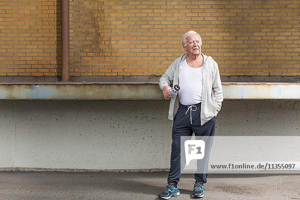 Mann in Sportkleidung hält Wasserflasche und schaut weg