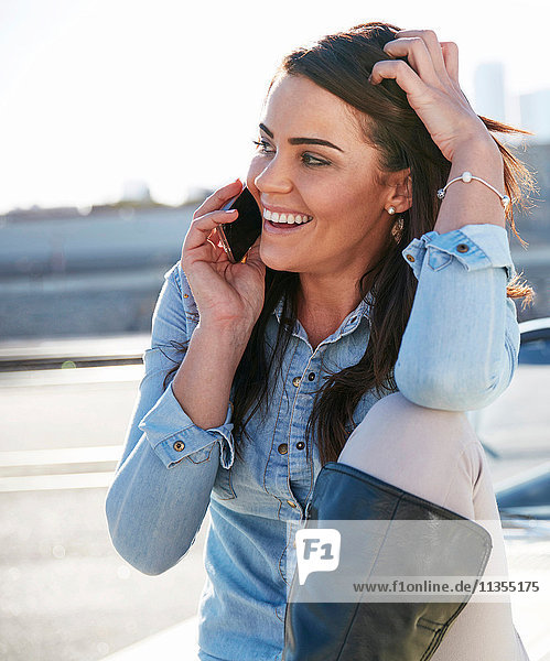 Woman by river making telephone call on smartphone