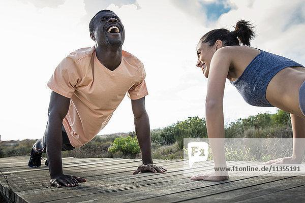 Couple doing push ups on wooden pathway