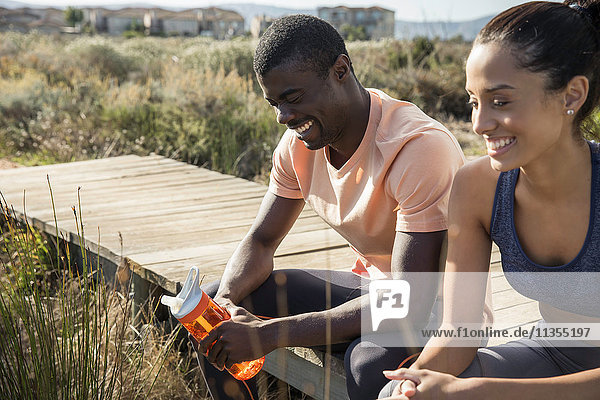 Couple wearing sports clothes sitting on wooden walkway