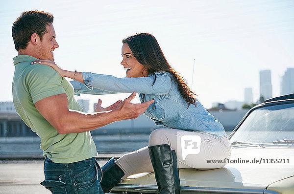 Ehepaar beim Herumalbern auf der Motorhaube eines Autos  Los Angeles  Kalifornien  USA