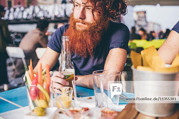 Junger männlicher Hipster mit roten Haaren und Bart  der Flaschenbier an der Bar trinkt.