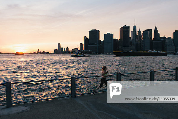 Young woman exercising outdoors  running by waterfront  Brooklyn  New York  USA