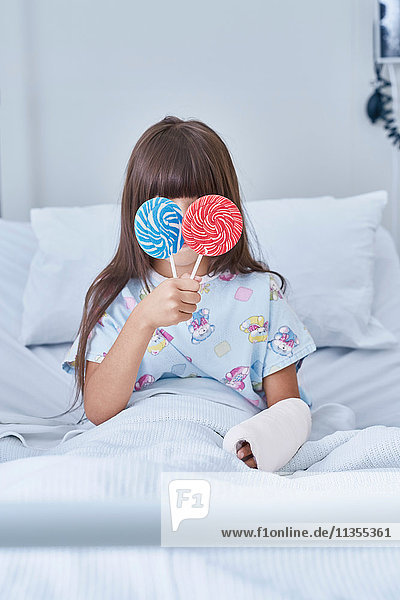 Portrait of girl patient holding lollipops in front of her eyes in hospital children's ward