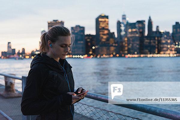 Junge Frau am Wasser  die ein Smartphone benutzt  Brooklyn  New York  USA