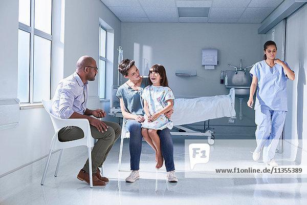 Männlicher Arzt im Gespräch mit Patientin und ihrer Mutter auf der Kinderstation im Krankenhaus