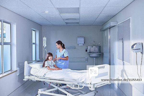 Krankenschwester  die den intravenösen Tropf für eine Patientin im Bett auf der Kinderstation des Krankenhauses einstellt