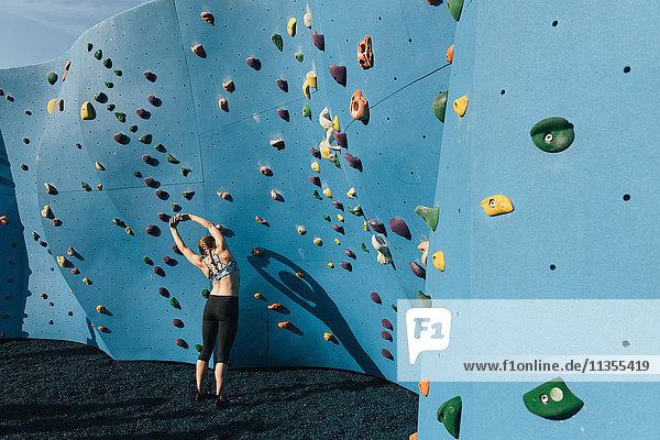 Young woman stretching  preparing to use climbing wall  Brooklyn Bridge Park  Brooklyn  New York  USA