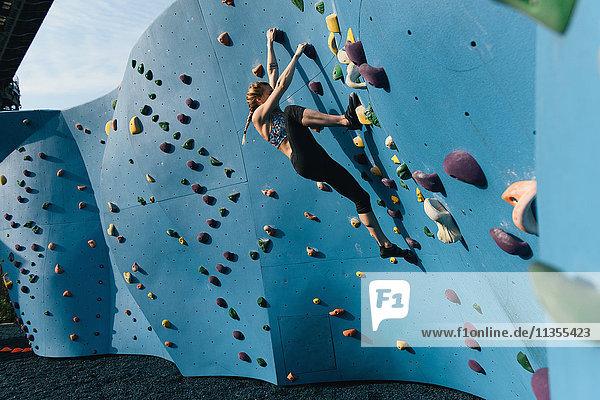 Young woman on climbing wall  Brooklyn Bridge Park  Brooklyn  New York  USA