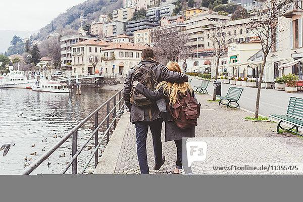 Rückansicht eines jungen Paares beim Spaziergang am Seeufer  Comer See  Italien