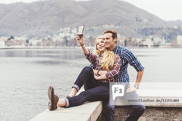 Junges Paar sitzt auf der Hafenmauer und nimmt Smartphone-Selfie mit  Comer See  Italien