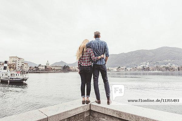 Rückansicht eines jungen Paares  das auf der Hafenmauer steht und hinaussieht  Comer See  Italien