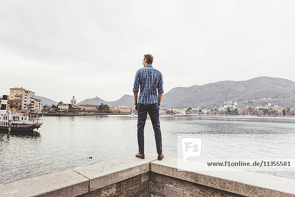 Rear view of young man standing on harbour wall looking out  Lake Como  Italy