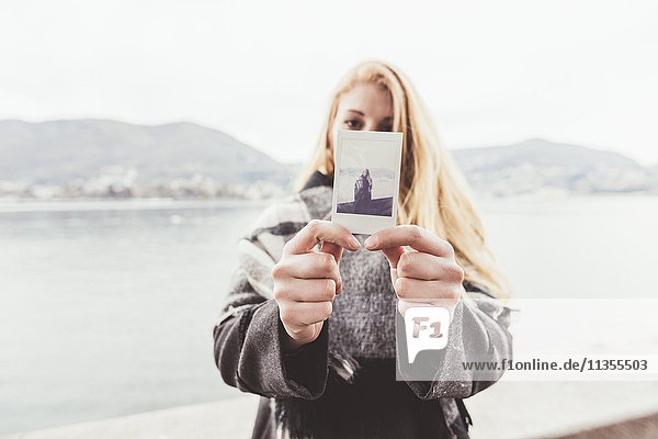 Portrait of young woman holding instant photograph of herself  Lake Como  Italy