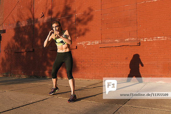 Young woman exercising outdoors  shadow boxing  Brooklyn  New York  USA