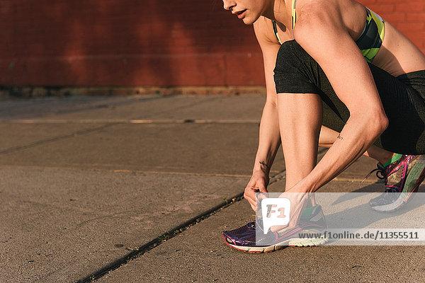 Junge Frau in Sportkleidung  hockend zum Schnürsenkelbinden  niedriger Abschnitt