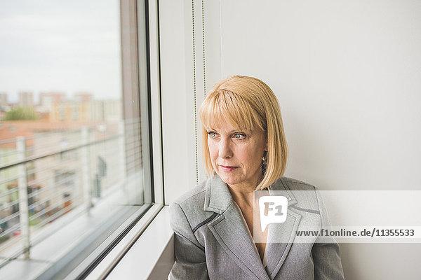Mature businesswoman staring through office window