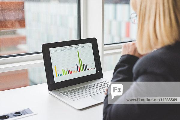 Über Schulteransicht der Geschäftsfrau beim Betrachten des Bargraphen auf dem Office-Laptop