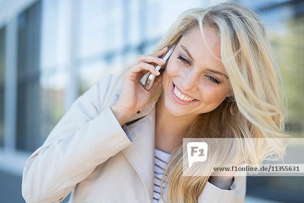Junge Frau  im Freien  mit Smartphone  lächelnd